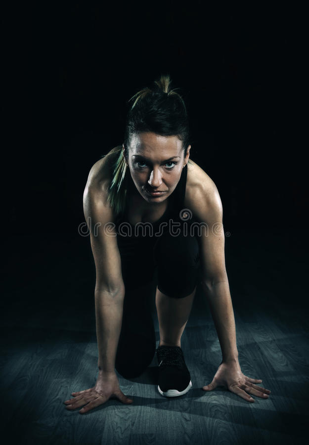 Athletic woman ready to run over dark background stock photo