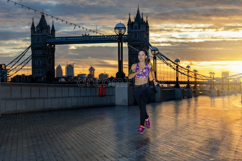Athletic woman running in front of the urban skyline of London royalty free stock images