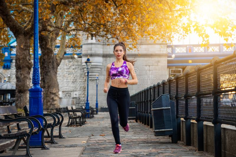 Athletic woman running at a riverside in the city of London, UK stock images