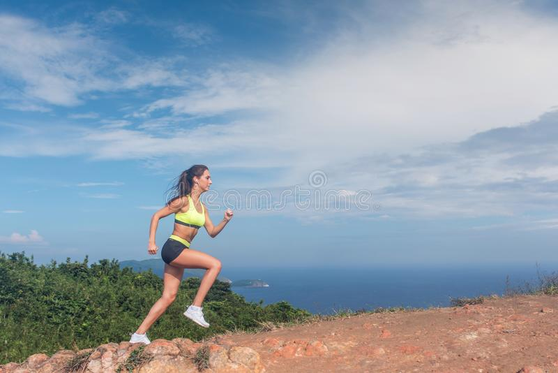 Athletic woman running up the mountain with sky and sea in background. Professional runner doing cardio work-out outdoor royalty free stock image