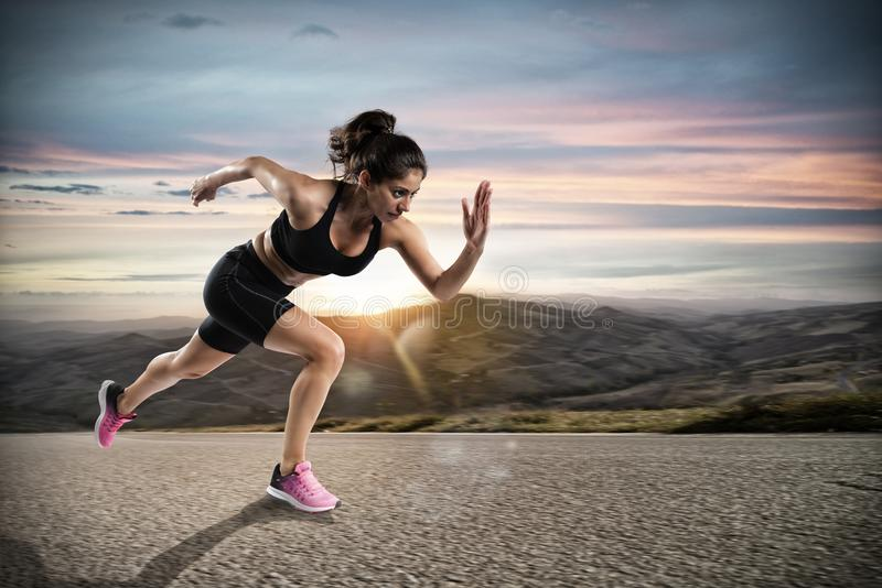 Athletic woman runs on the street during sunset stock image