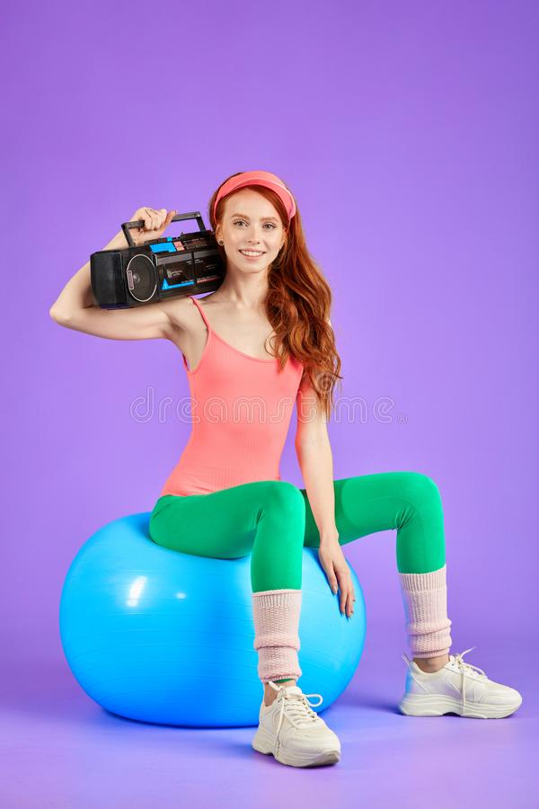 Athletic woman sitting on fitness ball with portable cassette player. Attractive athletic woman with long red curly hair sitting on fitness ball with portable royalty free stock photos