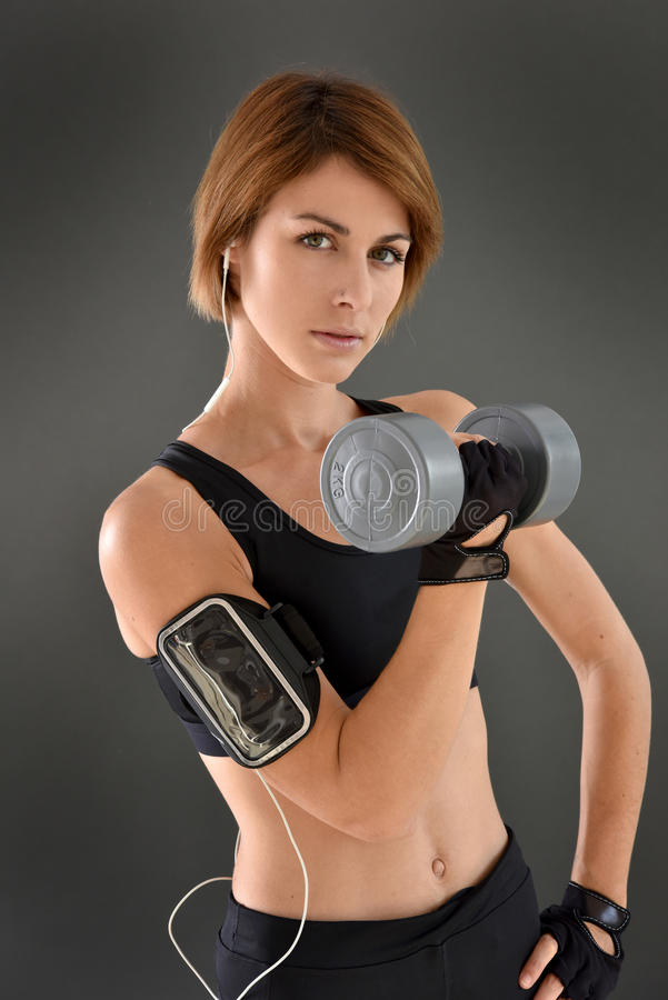 Athletic woman with smartphone and dumbbells royalty free stock image