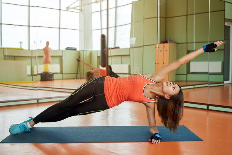 Athletic woman standing in pose plank on elbow, his hand moves to side, looking intently at  fingers of  hand.  stock photo
