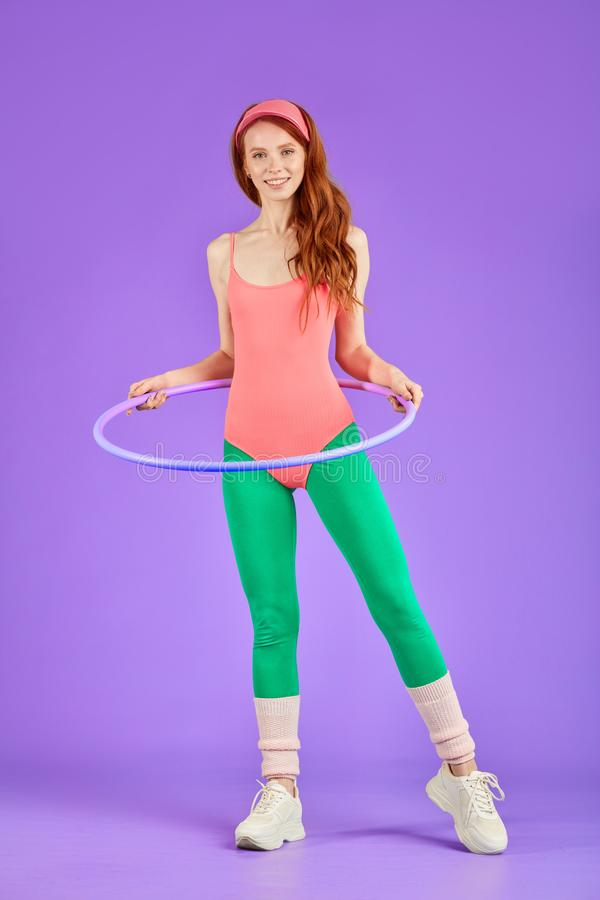 Athletic woman stands with hula hoop ready for fitness workout in gym stock photography