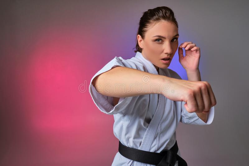 Athletic woman in traditional kimono is practicing karate in studio. Young attractive female with ponytail hair, dressed in a traditional kimono is looking at royalty free stock image