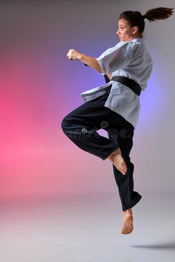 Athletic woman in traditional kimono is practicing karate in studio. Young charming girl with ponytail hair, dressed in a traditional kimono is practicing stock image