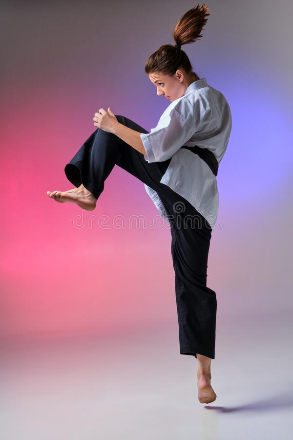 Athletic woman in traditional kimono is practicing karate in studio. Young charming lady with ponytail hair, dressed in a traditional kimono is practicing stock photos