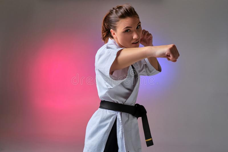 Athletic woman in traditional kimono is practicing karate in studio. Young gorgeous female with ponytail hair, dressed in a traditional kimono is practicing royalty free stock images