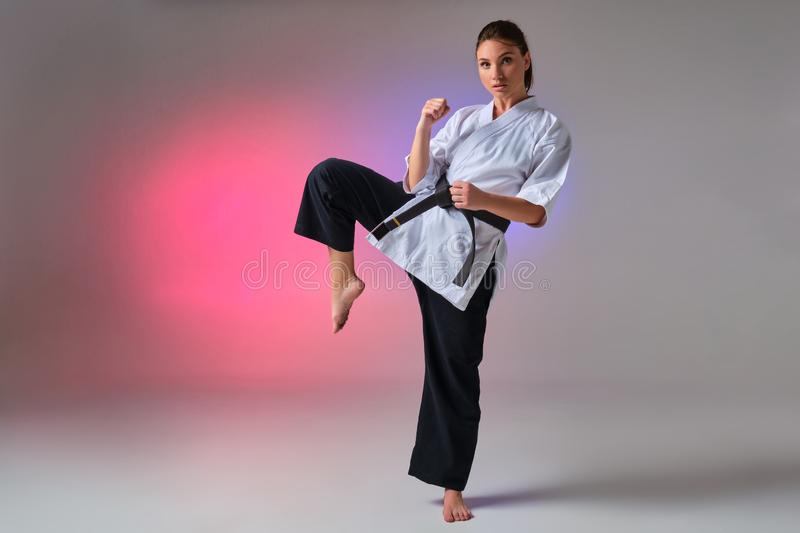 Athletic woman in traditional kimono is practicing karate in studio. Young gorgeous woman with ponytail hair, dressed in a traditional kimono is looking at the stock photo