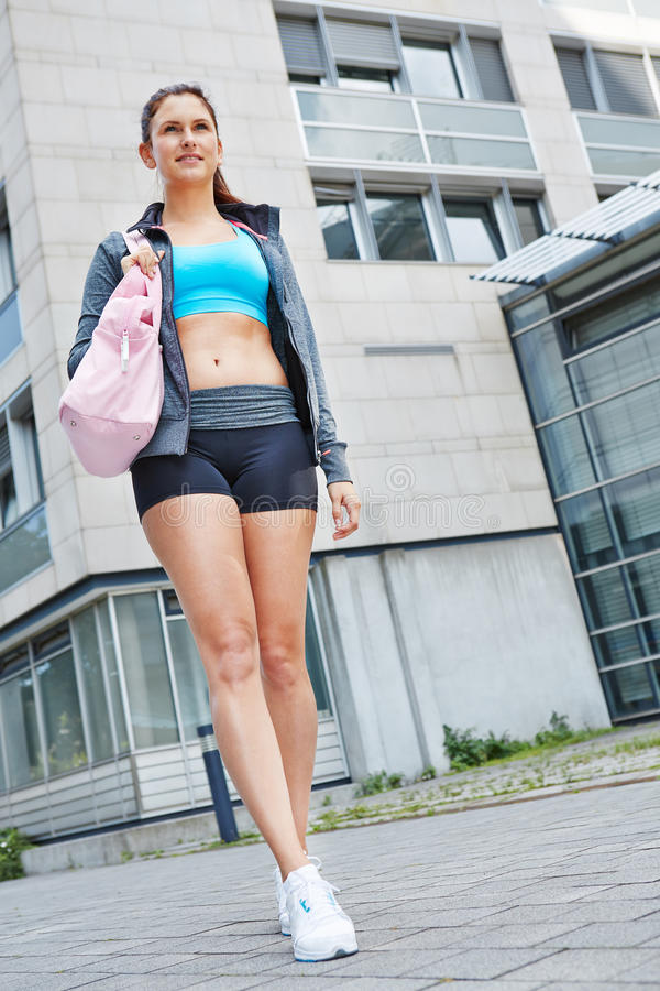 Athletic woman walking to fitness center stock photography