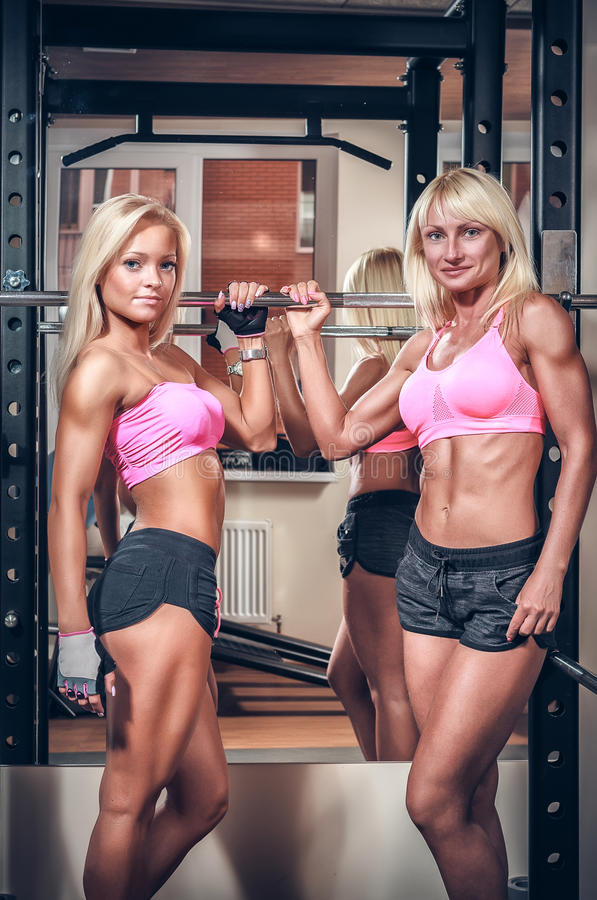 Athletic women showing muscles. Beautiful athletic women showing muscles stock image