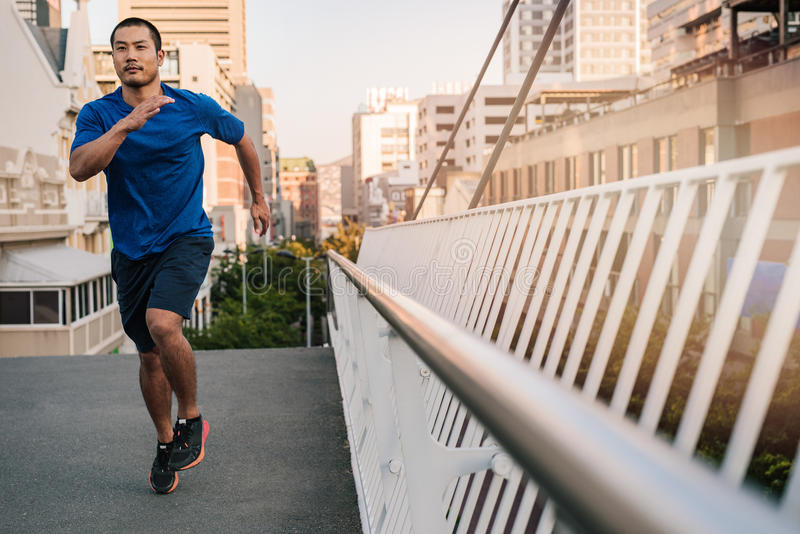 Athletic young Asian man running across a city bridge royalty free stock image