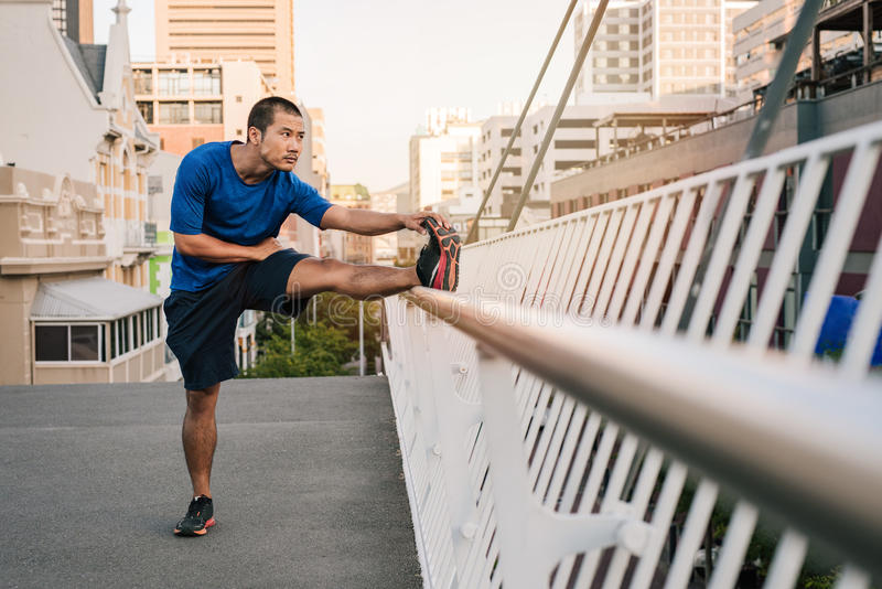 Athletic young Asian man stretching before a city run. Fit young Asian man in sportswear looking focused while stretching his legs on a railing before going for royalty free stock photography