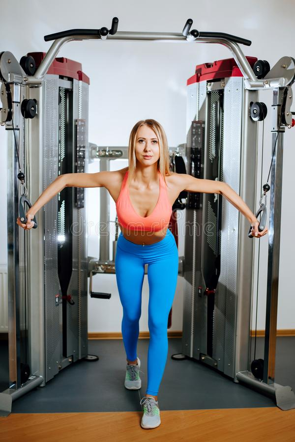 Athletic young blonde woman doing exercise on the chest in the crossover in the gym. Athletic young blonde woman doing exercise on the chest in the crossover in royalty free stock photo