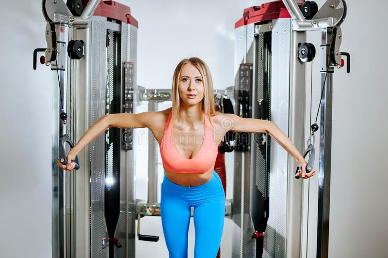 Athletic young blonde woman doing exercise on the chest in the crossover in the gym. Athletic young blonde woman doing exercise on the chest in the crossover in stock images