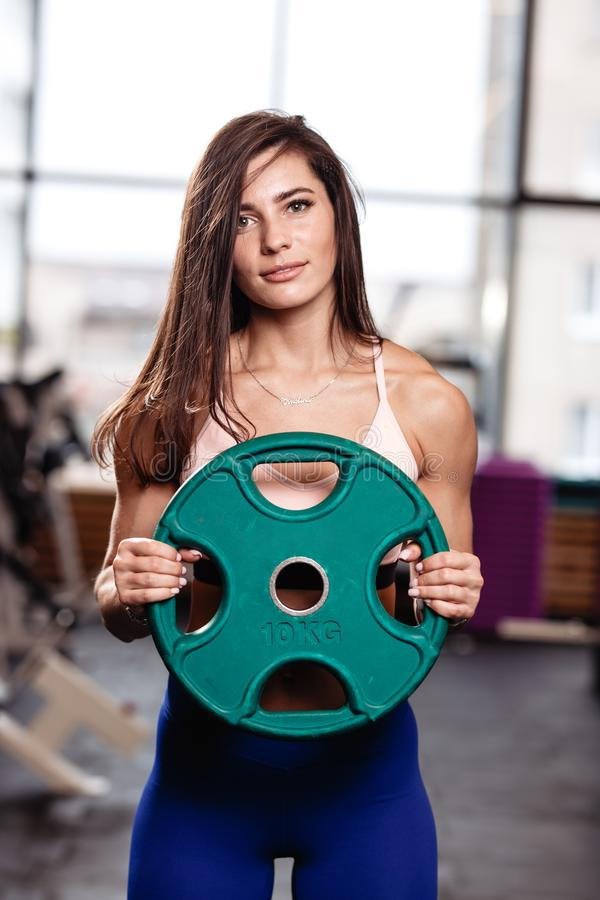 Athletic young brunette girl holds a heavy plate in her hands in the modern gym stock images