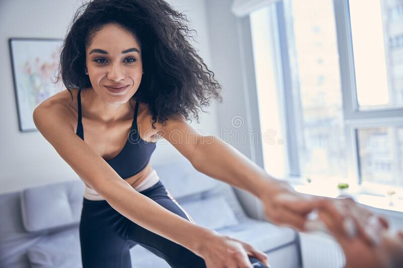 Athletic young female exercising in a room royalty free stock photos