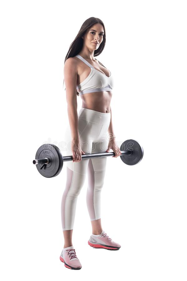 Athletic young fitness model gym woman posing while holding barbell looking at camera. royalty free stock images