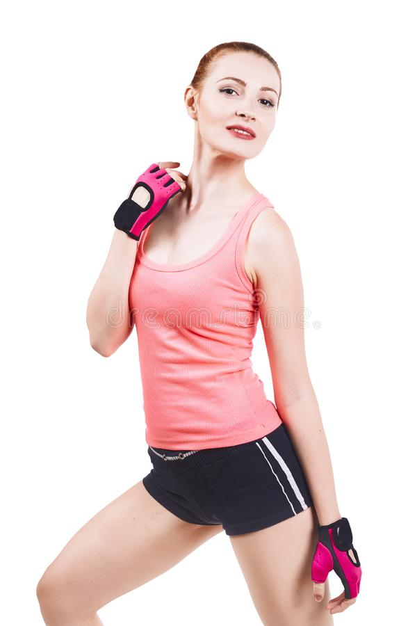 Athletic young fitness woman in sportswear posing over grey. Athletic young fitness redhead woman in pink sportswear posing over white stock photos