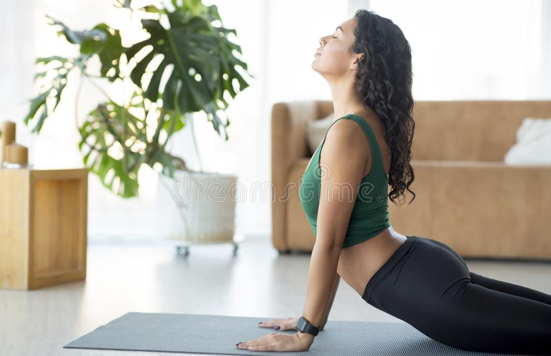 Athletic young girl doing yoga or stretching exercises on mat stock image