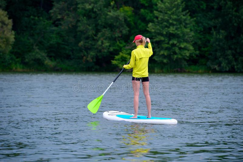 Athletic young girl-surfer riding on the stand-up paddle board in the clear waters of the on the background of green trees royalty free stock image