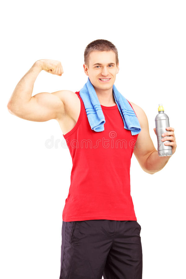Athletic young male in sportswear showing his muscles and holding a water bottle royalty free stock image