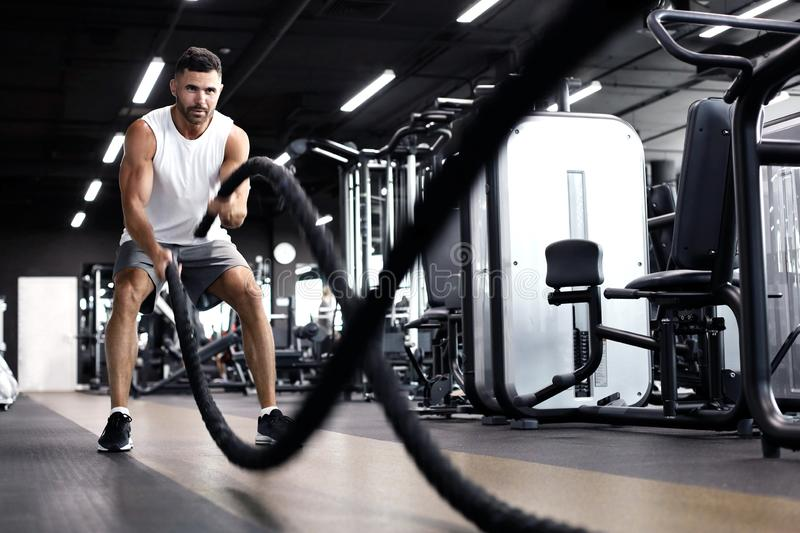 Athletic young man with battle rope doing exercise in functional training fitness gym royalty free stock photography