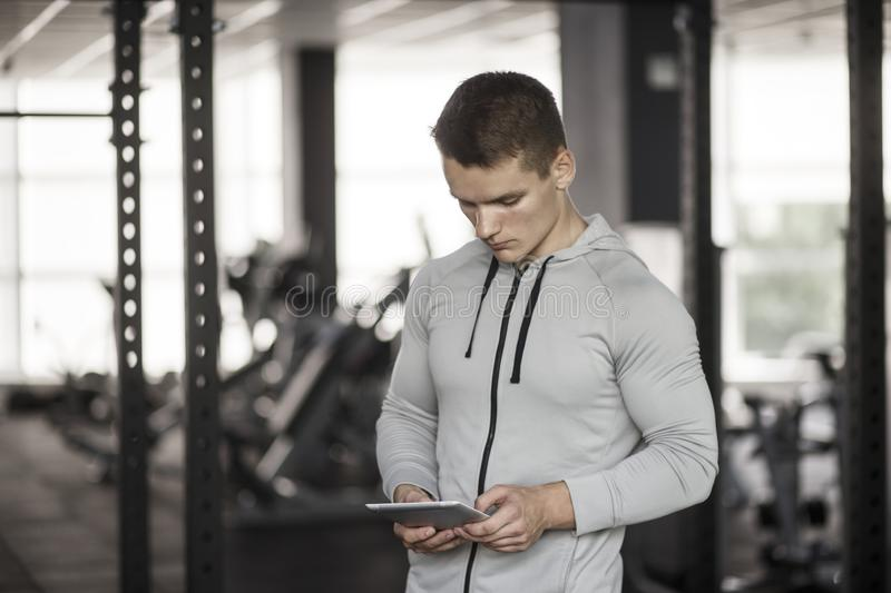 Athletic young man on digital tablet before training at gym, using application with workout plan. Bodybuilding concept stock photo