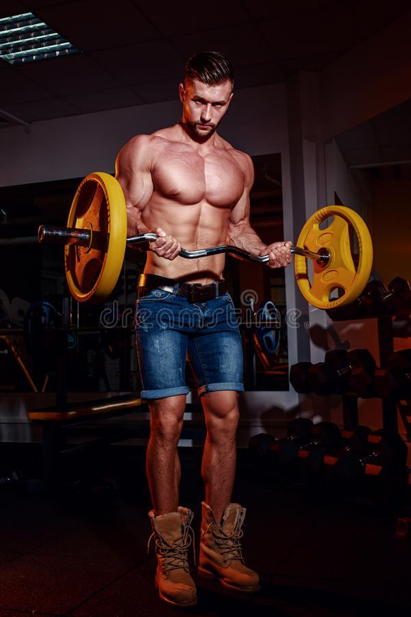 Athletic young man doing exercises with barbell in gym. Handsome muscular bodybuilder guy is working out. royalty free stock images
