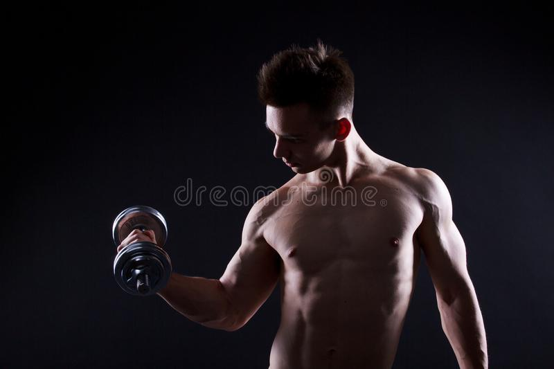 Athletic young man with a dumbbell on a black background. Naked torso, muscular body. Strong chest and shoulder muscles. Studio sh stock photos