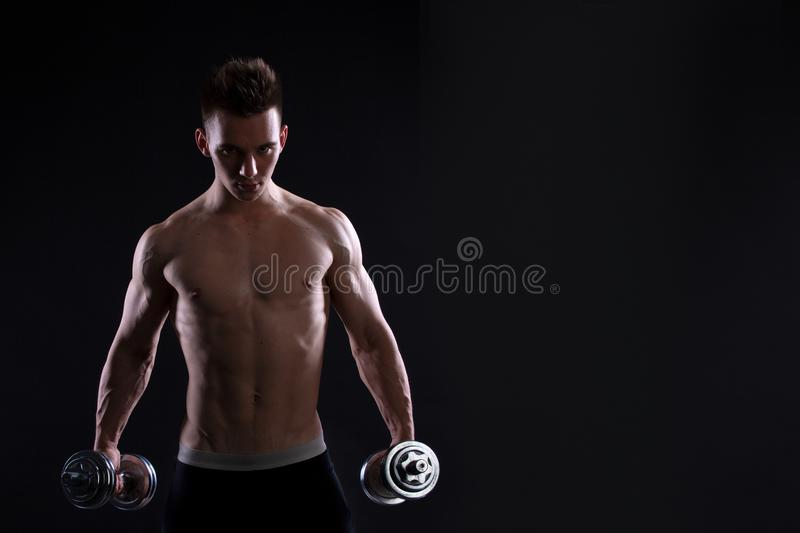 Athletic young man with a dumbbell on a black background. Naked torso, muscular body. Strong chest and shoulder muscles. Studio sh royalty free stock photo