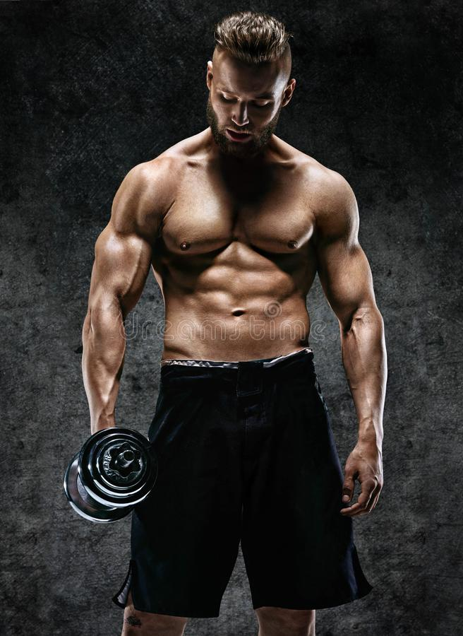 Athletic young man having a break. Photo of sporty muscular man with perfect body on dark background. Strength and motivation royalty free stock photography