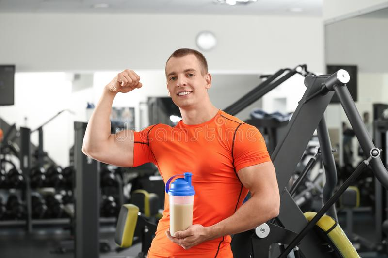 Athletic young man with protein shake royalty free stock photography