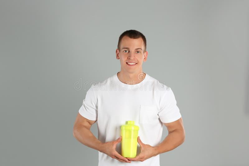 Athletic young man with protein shake on  grey background stock image