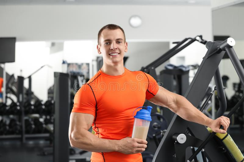 Athletic young man with  shake in gym royalty free stock photography