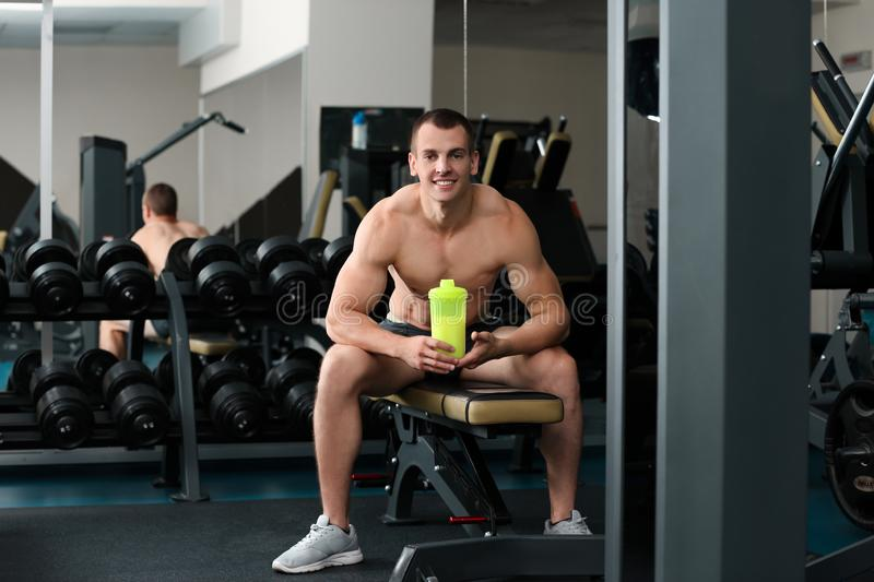 Athletic young man with  shake in gym royalty free stock image