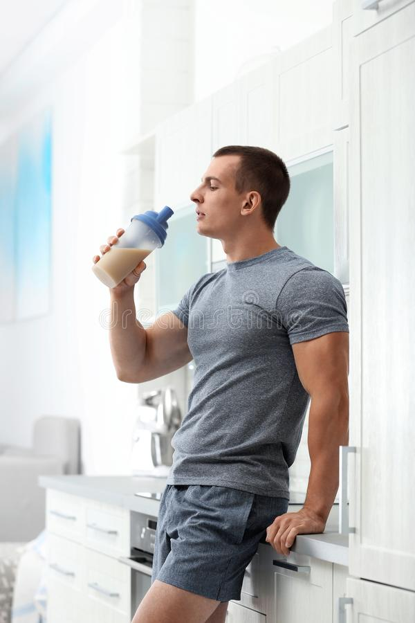 Athletic young man with  shake in kitchen royalty free stock images