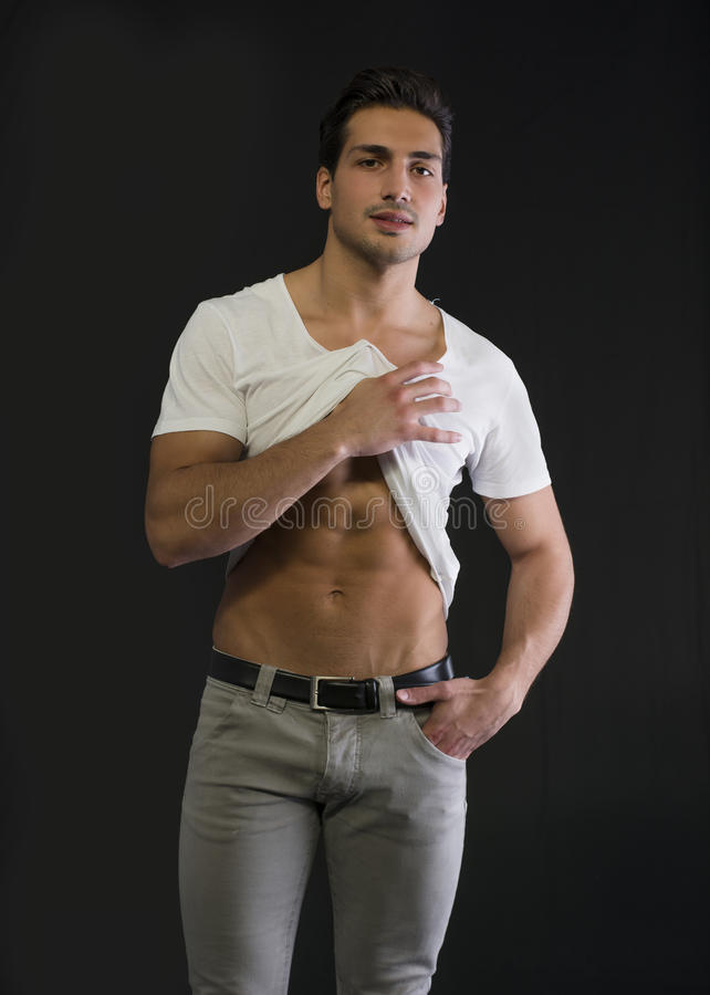 Athletic young man pulling up white t-shirt to show abs stock photography
