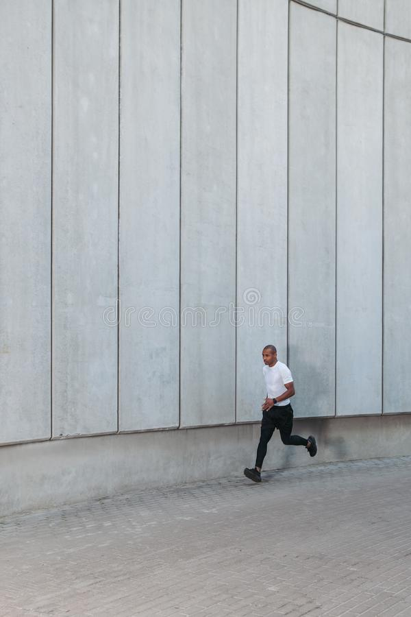 Athletic young man running. Man running in the urban space with  concrete wall on background. Healthy lifestyle stock photography