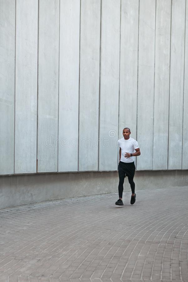 Athletic young man running. Man running in the urban space with  concrete wall on background. Healthy lifestyle royalty free stock photos
