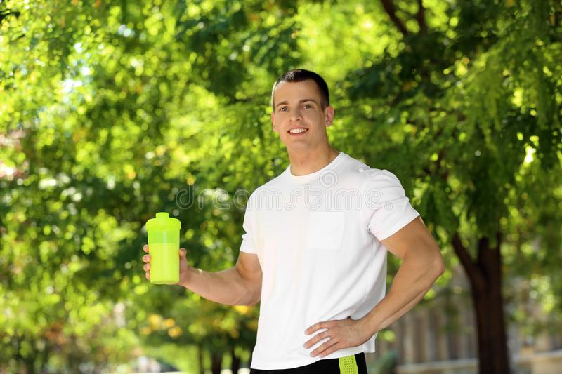 Athletic young man with  shake at green park stock photos