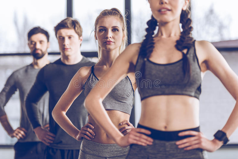 Athletic young people in sportswear exercising at the gym royalty free stock images