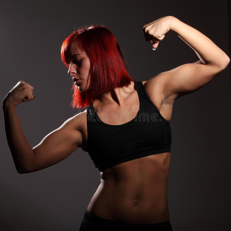 Athletic young strong woman on a dark background stock photography