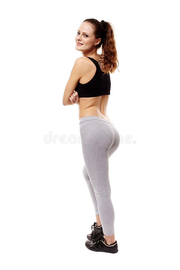 Athletic young woman with arms folded standing with the back at. Studio shot of an athletic young woman looking over shoulder with arms folded isolated over stock images