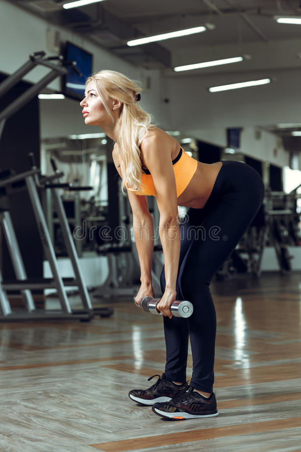 Athletic young woman doing exercises with dumbbells in gym royalty free stock photo