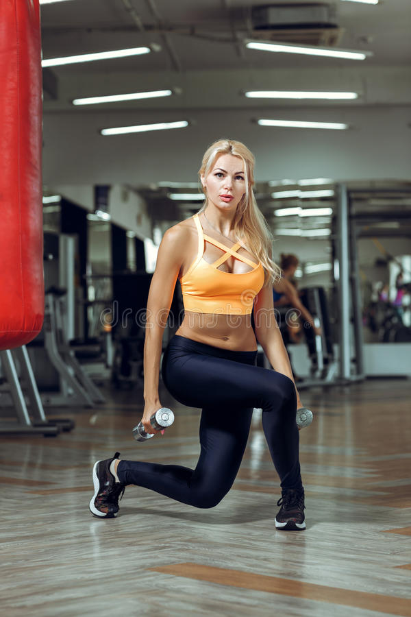 Athletic young woman doing exercises with dumbbells in gym royalty free stock photography