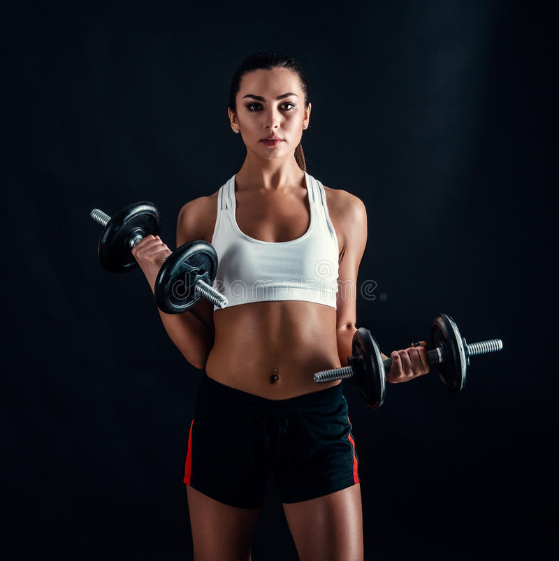 Athletic young woman doing a fitness workout against black background. Attractive fitness girl pumping up muscles with dumbbells. royalty free stock photo