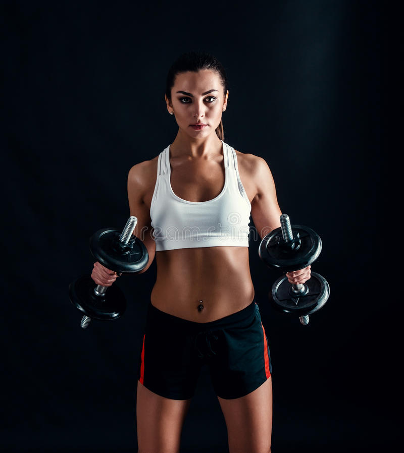 Athletic young woman doing a fitness workout against black background. Attractive fitness girl pumping up muscles with dumbbells. royalty free stock images