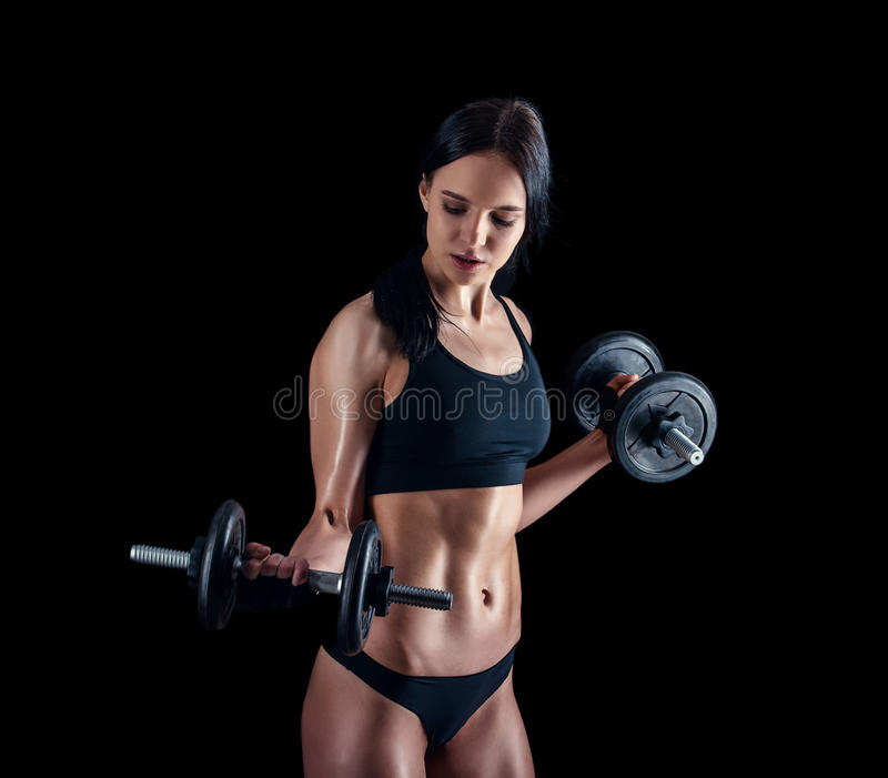 Athletic young woman doing a fitness workout against black background. Attractive fitness girl pumping up muscles with dumbbells. stock photo